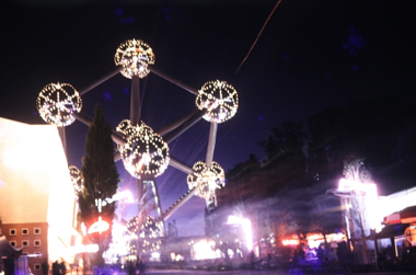Photo at night of a well lit atom-like structure.